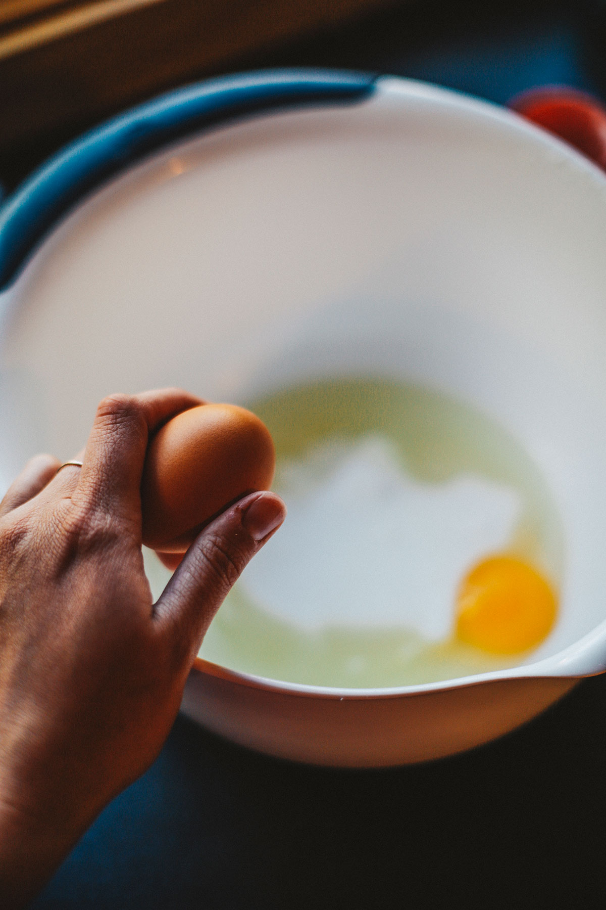 Breaking an egg into a mixing bowl