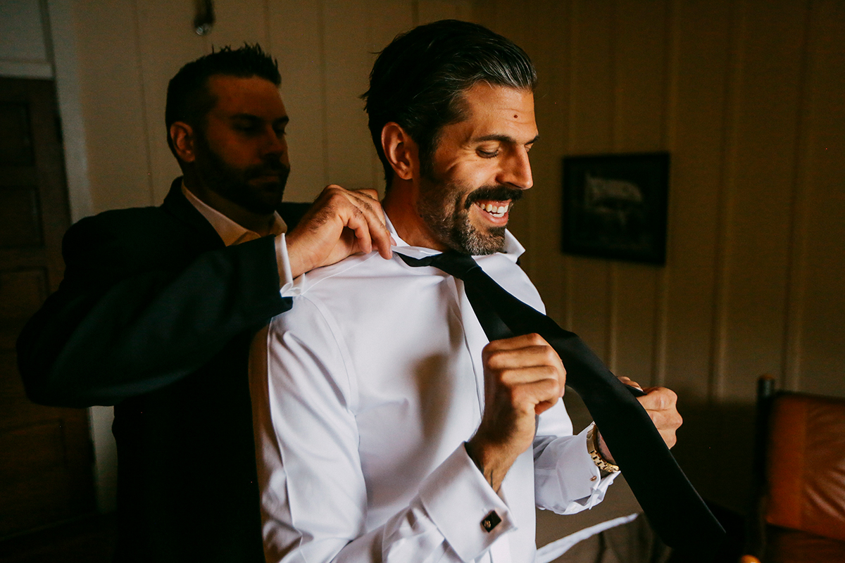 Groom and brother fixing tie