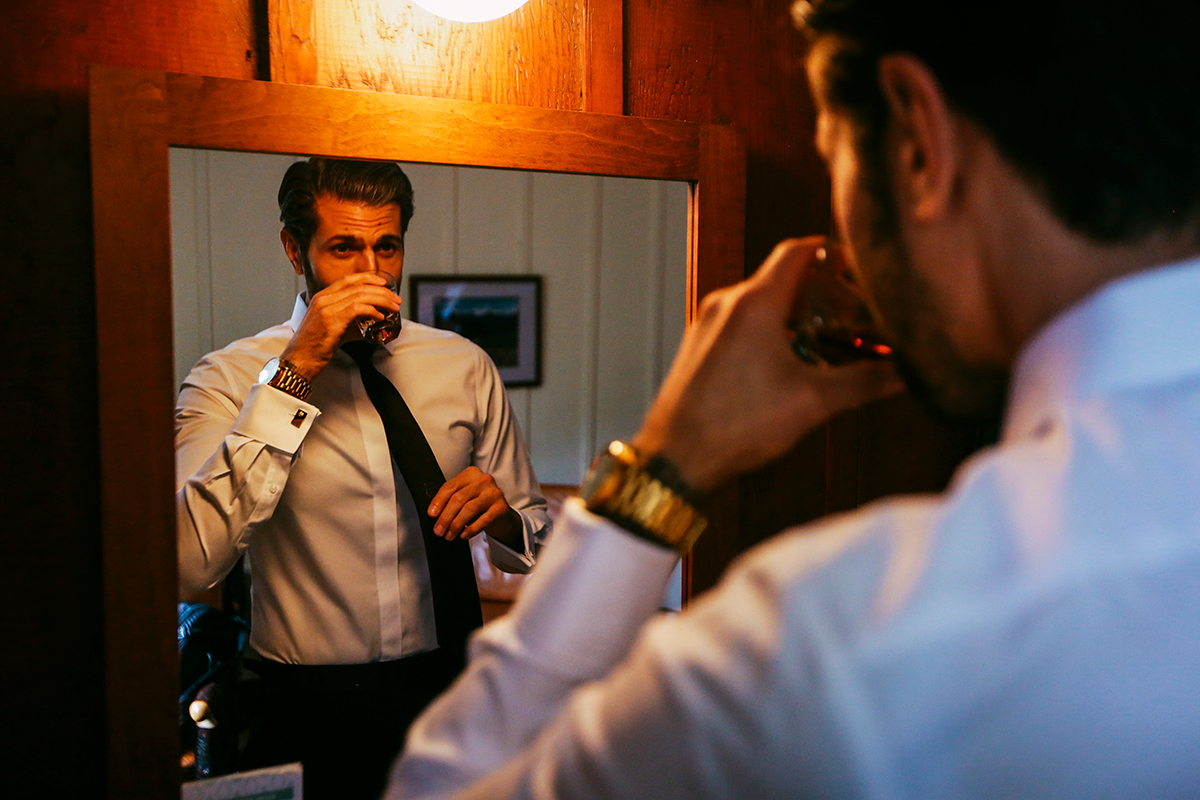 Groom looking into mirror