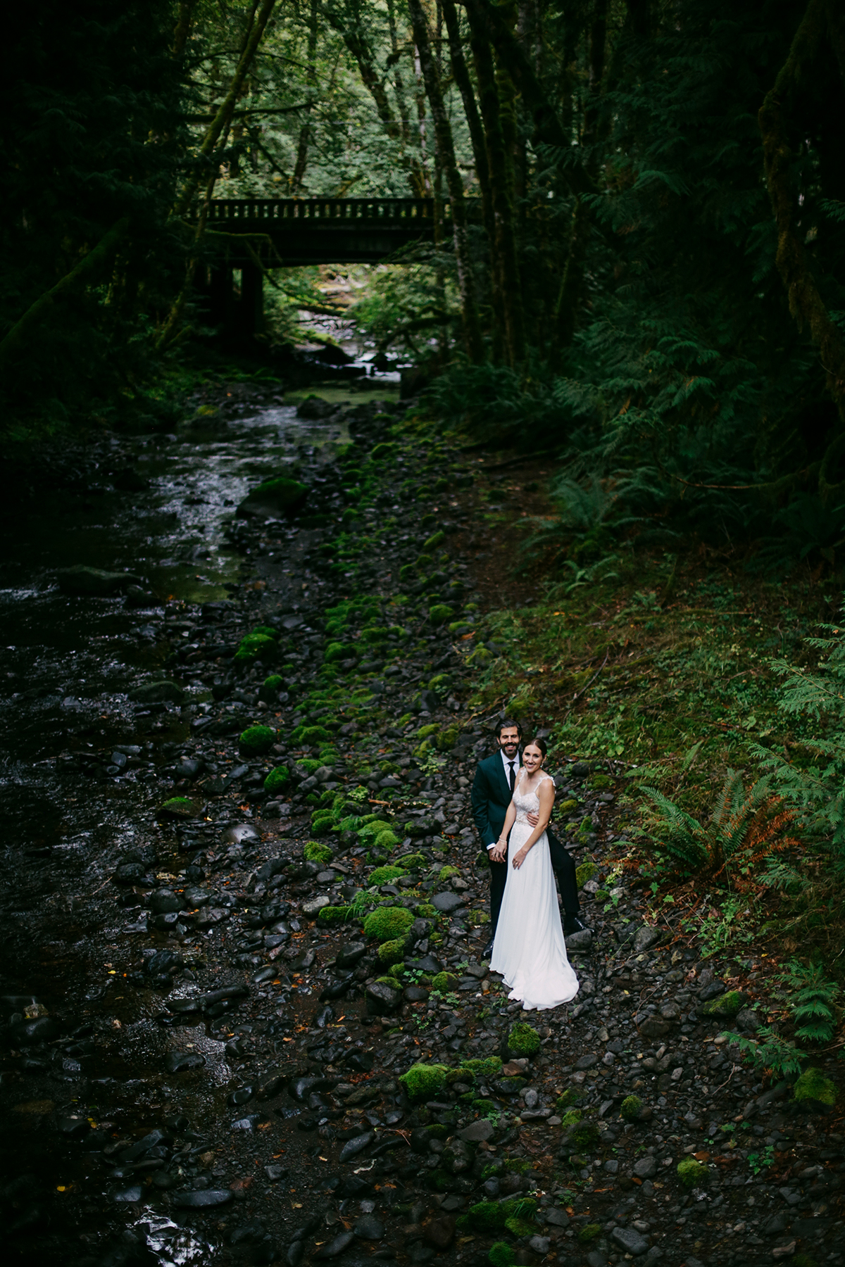 Bride and groom along river