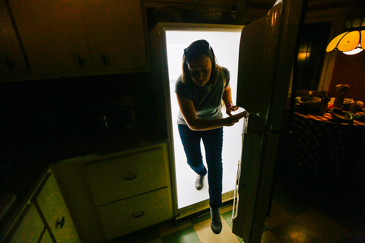Woman climbing out of refrigerator in Meow Wolf