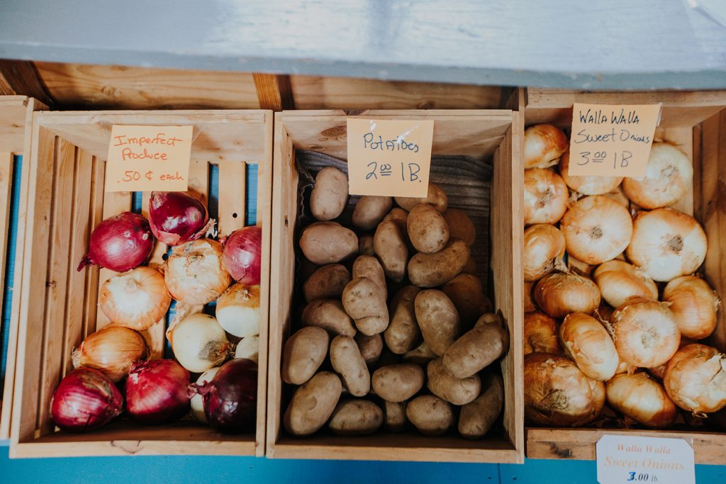 Imperfect produce, potatoes and Walla Walla Sweet Onions sit in bins at the Fruit des Vignes farm stand.